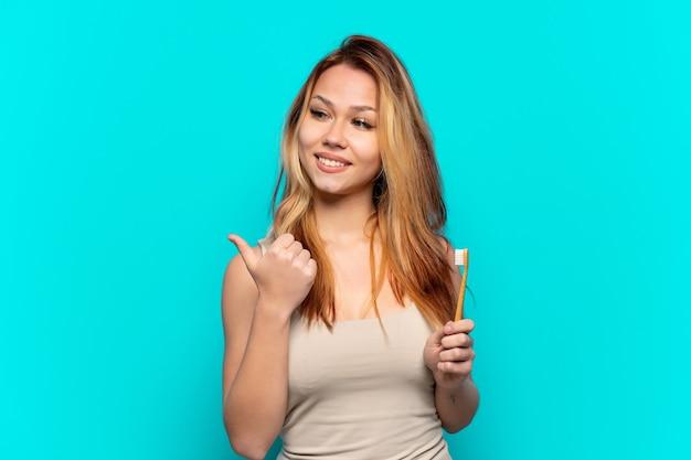 製品を提示する側を指している孤立した青い背景の上に歯を磨くティーンエイジャーの女の子
