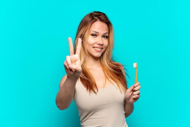 笑顔と勝利のサインを示す孤立した青い背景の上に歯を磨くティーンエイジャーの女の子