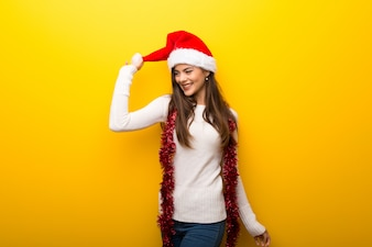 Teenager girl celebrating christmas holidays on vibrant yellow background