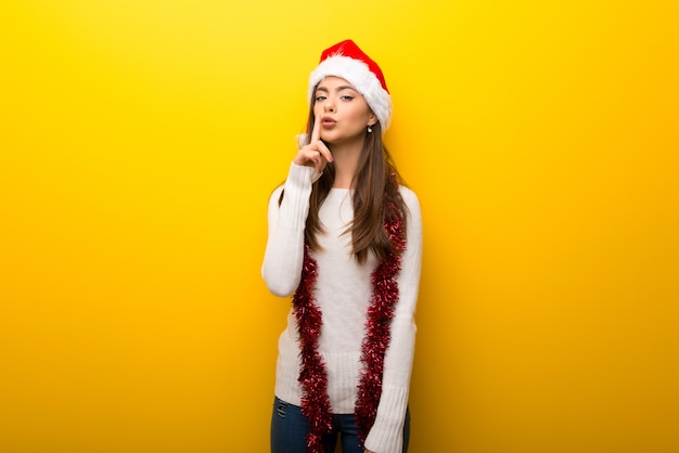 Teenager girl celebrating christmas holidays showing a sign of closing mouth and silence gesture