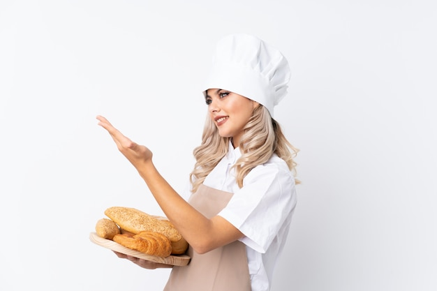 Teenager girl in chef uniform. female baker holding a table with several breads over isolated white  extending hands to the side for inviting to come