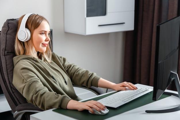 Девушка-подросток-киберспортсмен-геймер играет в компьютерную онлайн-игру дома одна в свободное время. молодая белокурая женщина в наушниках расслабляет компьютерную видеоигру игры пк и контролирует поток.