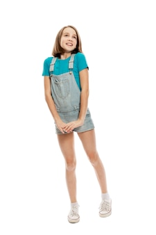 A teenager girl in denim overalls and a blue tank top emotionally jumps up. . vertical.