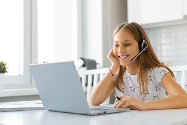Девушка-подросток делает домашнее задание дома. она смотрит на ноутбук. концепция онлайн-образования.