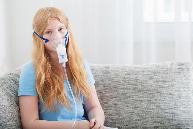 Teenager girl doing inhalation indoor