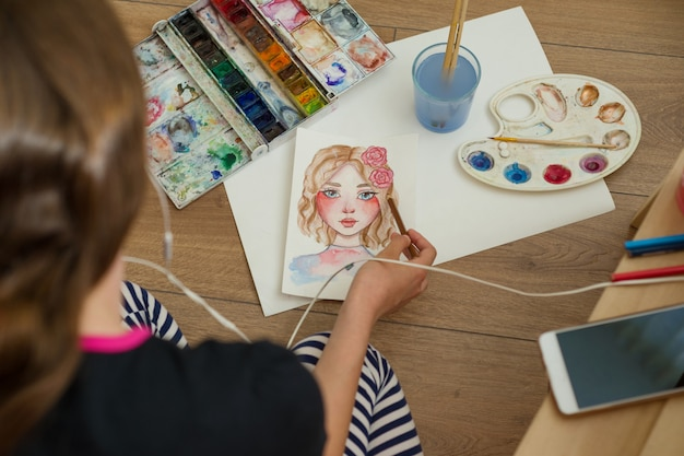 Teenager girl draws with watercolors, pencils