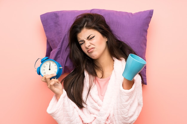 Teenager girl in dressing gown over pink backgrounnd and stressed holding vintage clock and holding a cup of coffee