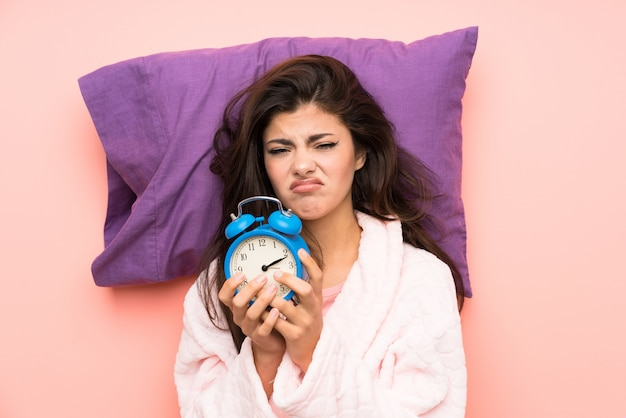 Teenager girl in dressing gown over pink backgrounnd and stressed holding vintage clock