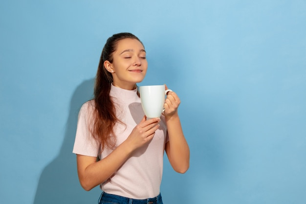 Ragazza dell'adolescente che gode del caffè