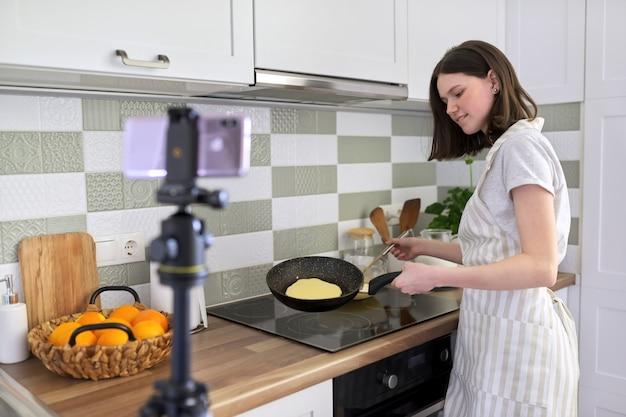 Девушка-подросток, пищевой блогер готовит блины с апельсином дома на кухне, снимает видео-рецепт. женщина со сковородой возле плиты. хобби, видеоканал с подписчиками, дети и подростки