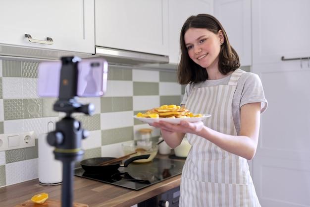 Девушка-подросток, пищевой блогер готовит блины с апельсином дома на кухне, снимает видео-рецепт. самка с готовой едой, приятного аппетита. хобби, видеоканал с подписчиками, дети и подростки