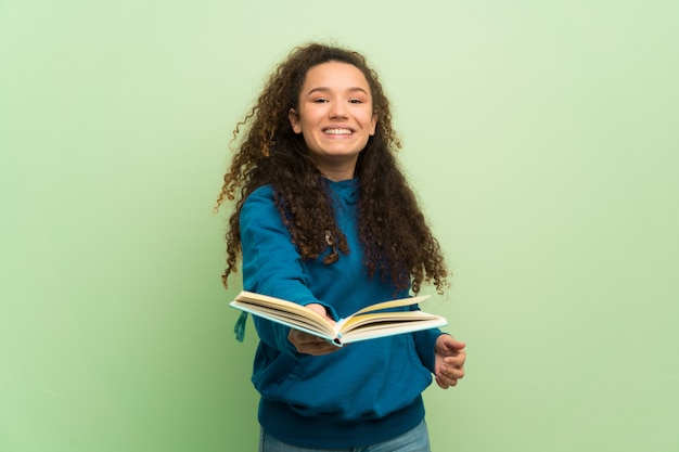 Teenager girl over green wall holding a book and giving it to someone