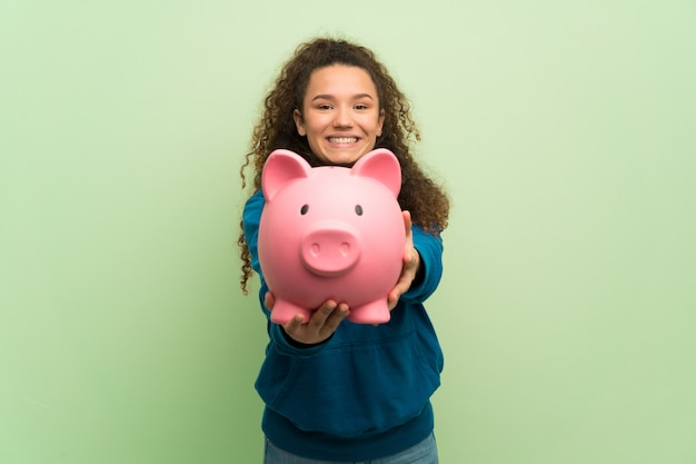Teenager girl over green wall holding a piggybank