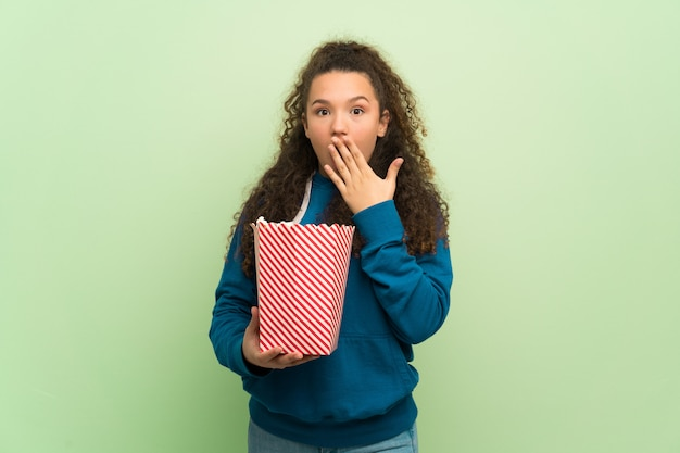 Teenager girl over green wall surprised and eating pop corns