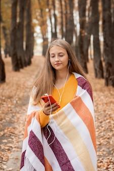 Девушка-подросток гуляет в парке и наслаждается своими любимыми песнями, любуясь красотой природы