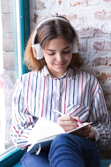 Teenager girl in headphones sitting with open notebook and writing by hand