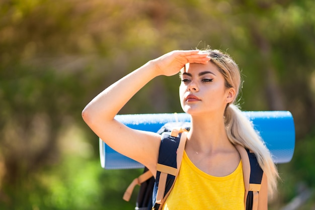 Teenager girl hiking at outdoors looking far away with hand to look something