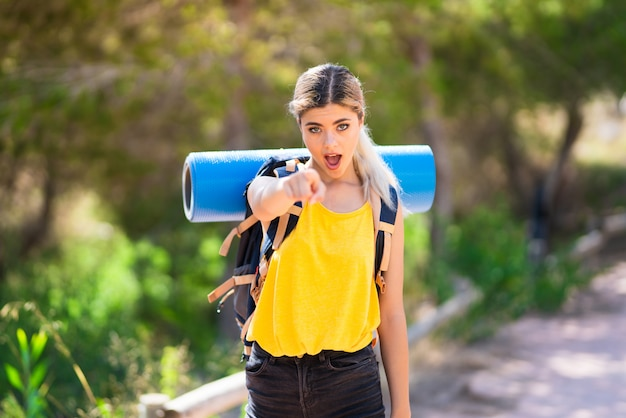 Teenager girl hiking at outdoors surprised and pointing front