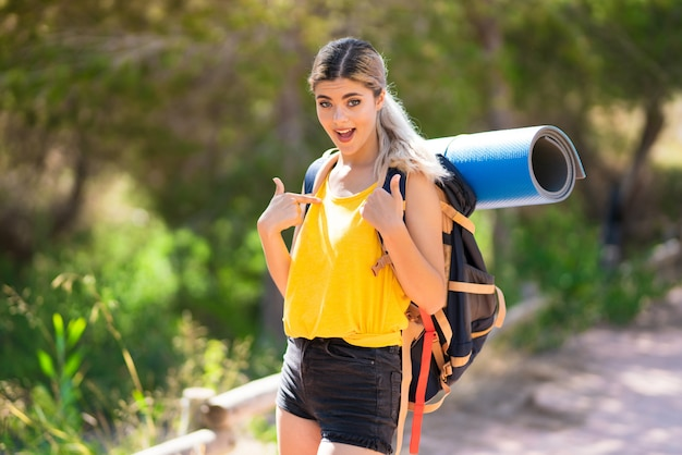 Teenager girl hiking at outdoors with surprise facial expression