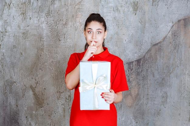 Девушка-подросток держит синюю подарочную коробку, обернутую белой лентой, и выглядит напряженной или напуганной.