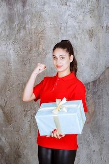 파란색 선물 상자를 들고 십 대 소녀 흰색 리본으로 포장 하 고 즐거움 손 기호를 보여주는.