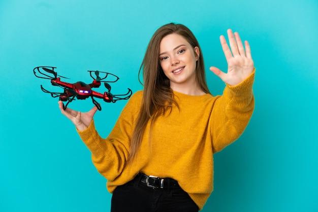 Девушка-подросток держит дрон на изолированном синем фоне, считая пять пальцами