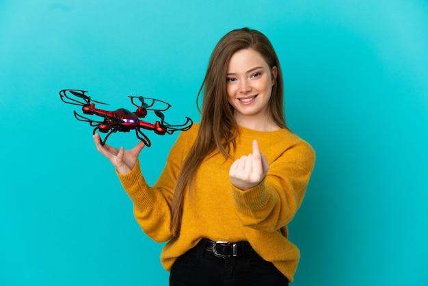 Девушка-подросток держит дрон на изолированном синем фоне, делая приближающийся жест