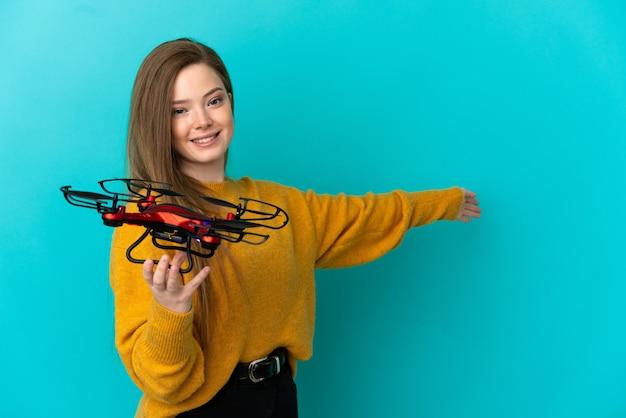 Девушка-подросток держит дрон на изолированном синем фоне, протягивая руки в сторону, приглашая приехать
