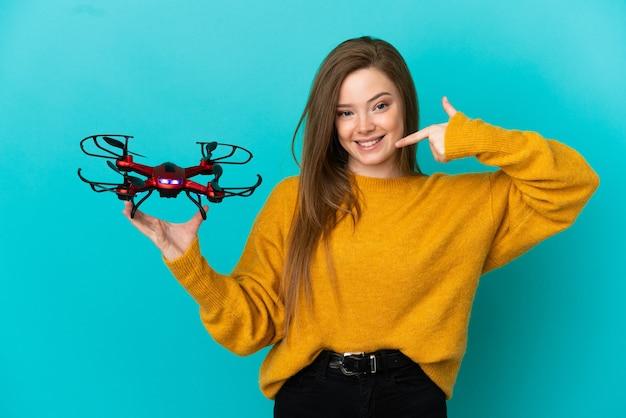 Девушка-подросток держит дрон на изолированном синем фоне, показывая большой палец вверх