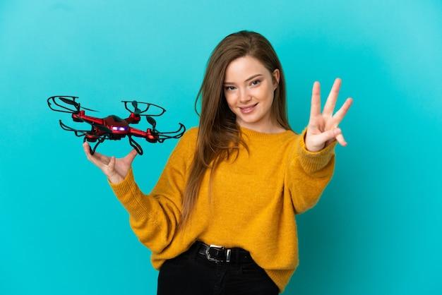 Девушка-подросток держит дрон на изолированном синем фоне счастлива и считает три пальцами