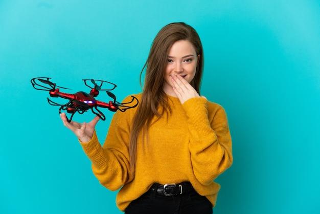 Девушка-подросток держит дрон на изолированном синем фоне, счастливая и улыбающаяся, прикрывая рот рукой