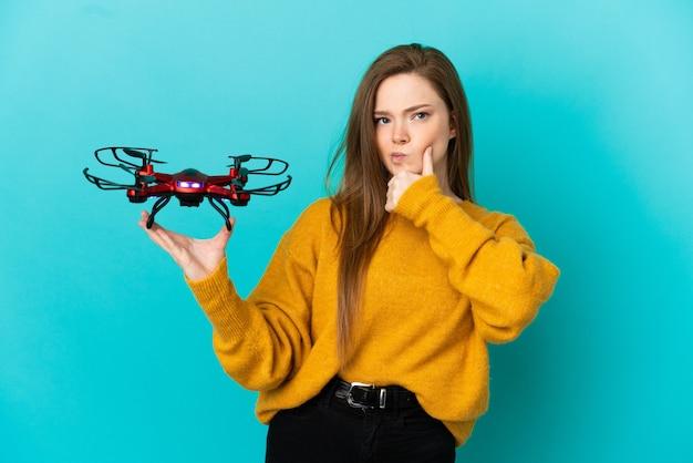Девушка-подросток держит дрон на изолированном синем фоне, сомневаясь и думая