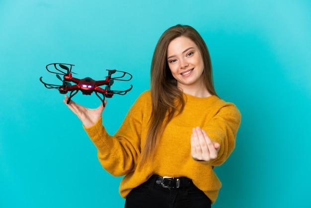 Девушка-подросток держит дрон на изолированном синем фоне, приглашая прийти с рукой. счастлив что ты пришел