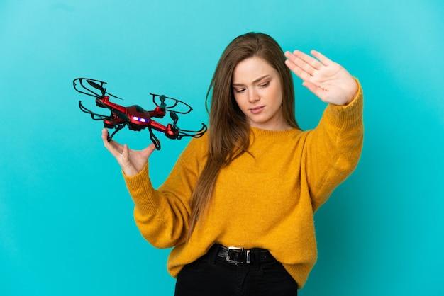 Девушка-подросток держит дрон на изолированном синем фоне, делая жест стоп и разочарована