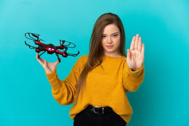 Девушка-подросток держит дрон на изолированном синем фоне, делая стоп-жест