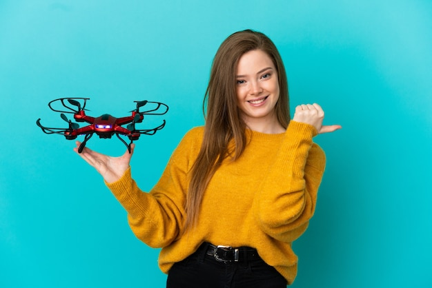 Девушка-подросток держит дрон на изолированном синем фоне, указывая в сторону, чтобы представить продукт