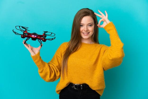 Девушка-подросток держит дрон на изолированном синем фоне, показывая пальцами знак ок