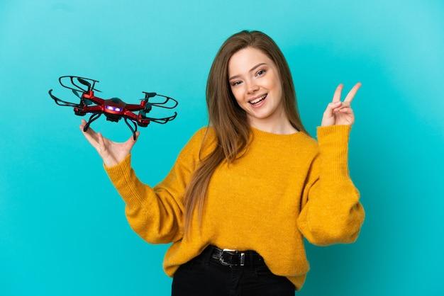 Девушка-подросток держит дрон на изолированном синем фоне, улыбаясь и показывая знак победы