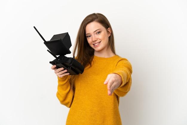 Девушка-подросток держит пульт дистанционного управления дроном на изолированном белом фоне, пожимая руку для заключения хорошей сделки