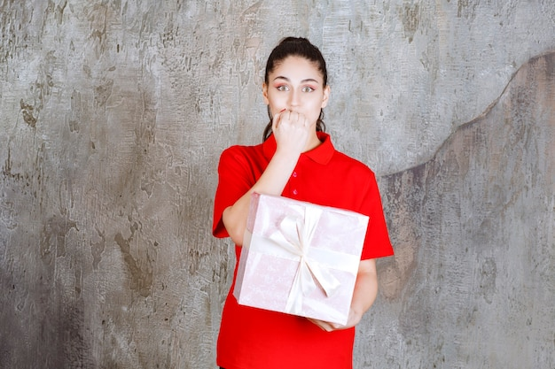 白いリボンで包まれたピンクのギフトボックスを持っているティーンエイジャーの女の子は、ストレスと緊張に見えます。