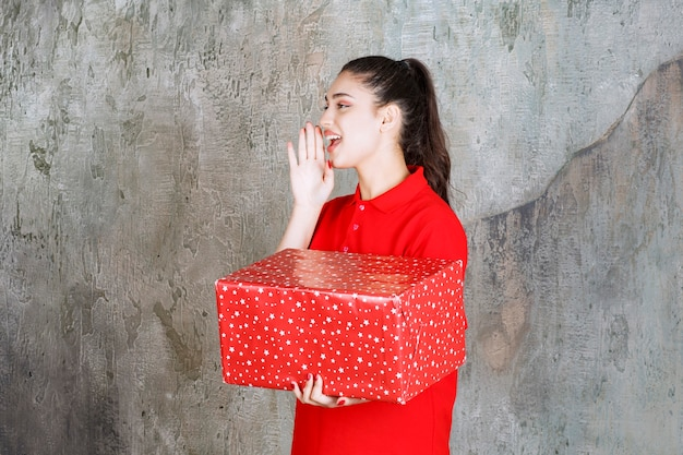 Девушка-подросток держит красную подарочную коробку с белыми точками и зовет кого-то.