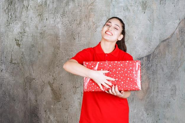 그것에 흰색 점이있는 빨간색 선물 상자를 들고 십 대 소녀.