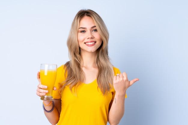 製品を提示する側を指している青に分離されたオレンジジュースを保持している10代の少女
