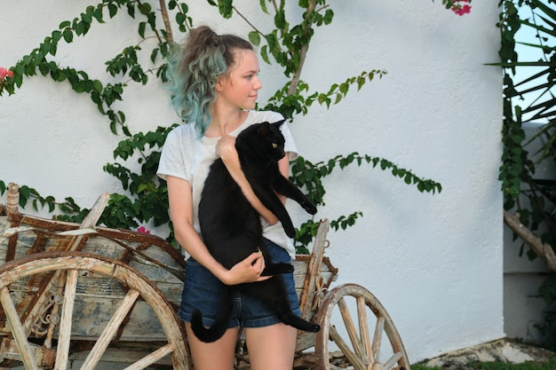 Teenager girl holding big black cat in her arms, outdoor, summer sunny day