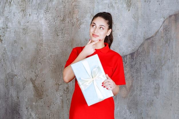 Ragazza adolescente che tiene una scatola regalo blu avvolta con un nastro bianco e sogna o ha una buona idea