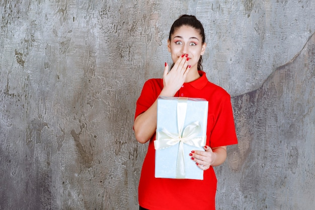 Teenager girl holding a blue gift box wrapped with white ribbon and looks stressed or terrified