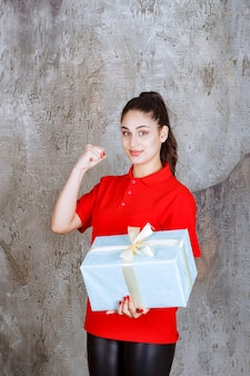 Teenager girl holding a blue gift box wrapped with white ribbon and showing enjoyment hand sign.