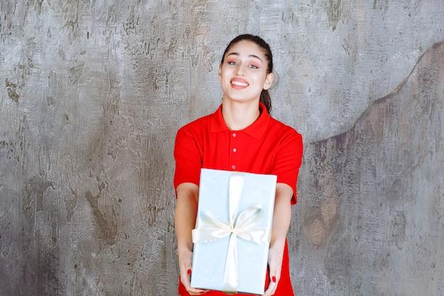 Ragazza dell'adolescente che tiene un contenitore di regalo blu avvolto con nastro bianco.
