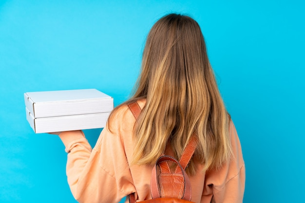 Teenager girl holding a box of pizzas over isolated blue wall