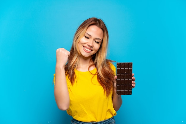 Teenager girl holding chocolat over isolated blue background celebrating a victory